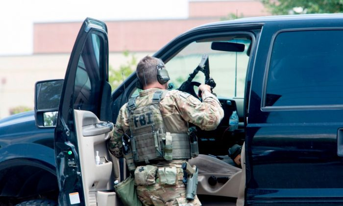An FBI agent is seen in the parking lot of Santa Fe High School where at least eight people were killed on May 18, 2018 in Santa Fe, Texas. (Daniel Kramer/AFP/Getty Images)