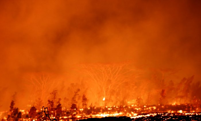 Lava flows through forest on the outskirts of Pahoa during ongoing eruptions of the Kilauea Volcano in Hawaii, U.S., May 18, 2018.  (Reuters/Terray Sylvester)