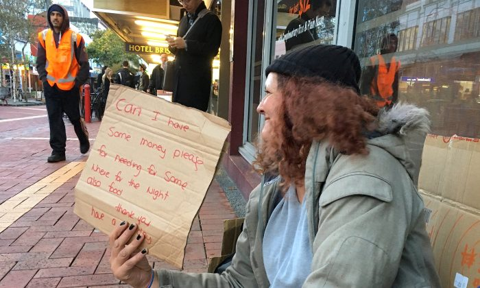 A woman, known only as Margaret and claiming to be homeless, holds a sign as she begs for money on a main street in central Wellington, New Zealand, May 15, 2018. (REUTERS/Jonathan Barrett/File Photo)