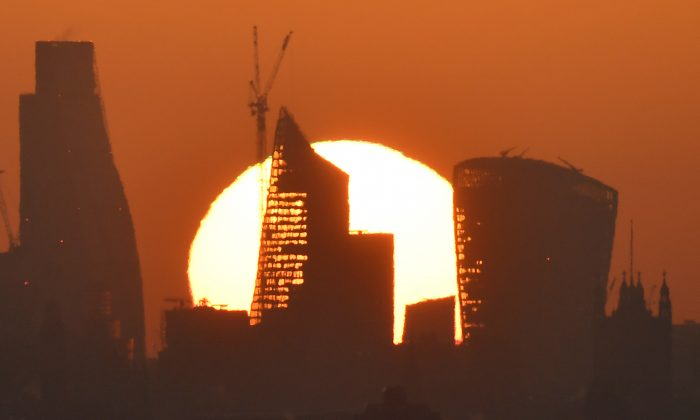 The sun is seen rising over skyscrapers in the City of London financial district in London, Britain, May 3, 2018. (Reuters/Toby Melville)