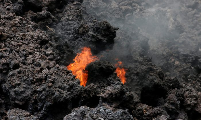 Flames are seen in a lava flow on Highway 137 southeast of Pahoa during ongoing eruptions of the Kilauea Volcano in Hawaii, U.S., May 20, 2018. (Reuters/Terray Sylvester)