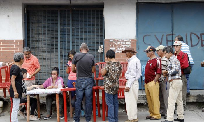 "Venezuelan citizens check in at a ""Red Point,"" an area set up by President Nicolas Maduro's party, to verify that they cast their votes during the presidential election in Barquisimeto, Venezuela, May 20, 2018. (Reuters/Carlos Jasso)"