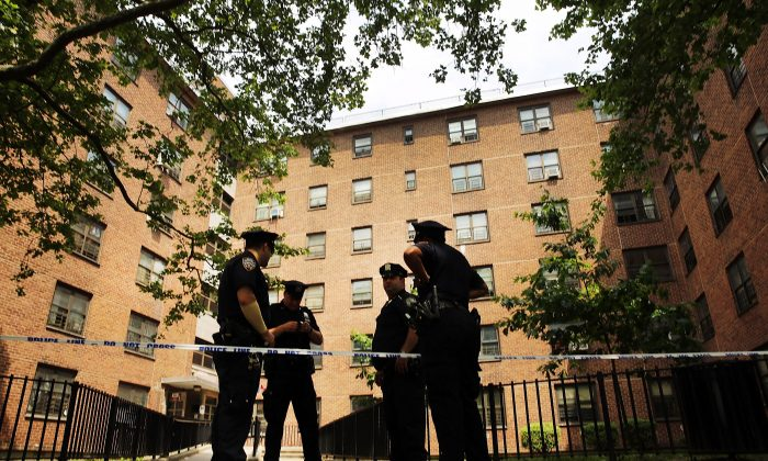 Police stand near the entrance to the building where two children were attacked with a knife in an East New York neighborhood apartment building elevator on June 4, 2014 in the Brooklyn borough of New York City.  (Spencer Platt/Getty Images)