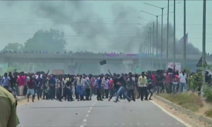 People pelt stones during a protest against the construction of a copper smelter by Vedanta Resources from the road, in Thoothukudi, Tamil Nadu, India in this still image from May 22, 2018.  (ANI via REUTERS TV)