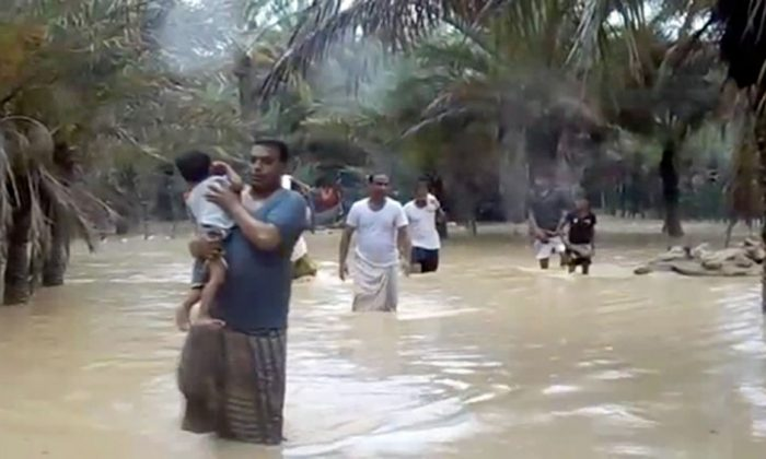 An image grab taken from an AFPTV video shows people walking through flood water as they evacuate a flooded area during a cyclone in the Yemeni island of Socotra, May 24, 2018. (Stringer/AFP/Getty Images)
