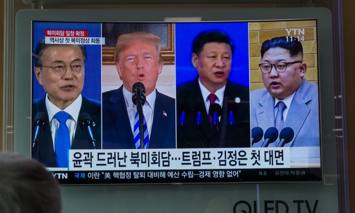 People watch a screen showing images of (L-R) South Korea's president Moon Jae-in, U.S. president Donald Trump, China's leader Xi Jinping, and North Korea's leader Kim Jong Un at a railway station in Seoul on May 11, 2018. (KIM SUE-HAN/AFP/Getty Images)