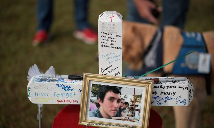 A photo of Christian Garcia hangs on a cross at a memorial in front of Santa Fe High School on May 22, 2018 in Santa Fe, Texas. The makeshift memorial honors the victims of last Friday's shooting when 17-year-old student entered the school with a shotgun and a pistol and opened fire, killing 10 people.  (Scott Olson/Getty Images)