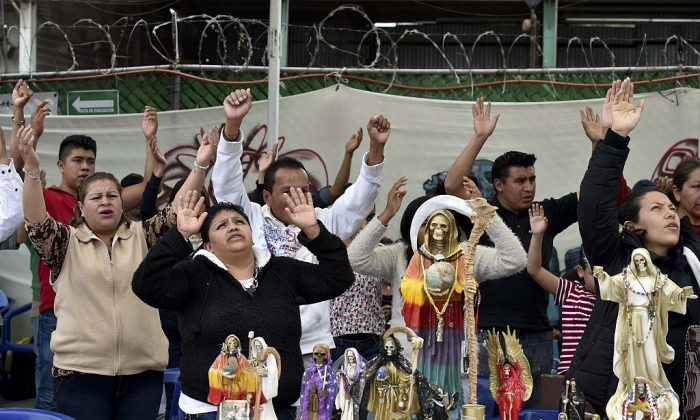 """People pray in front of figures of Santa Muerte, or """"Saint Death,"""" condemned by the Catholic church as Satanic, in Mexico on Feb. 7, 2016. (Yuri Cortez/AFP/Getty Images)"""