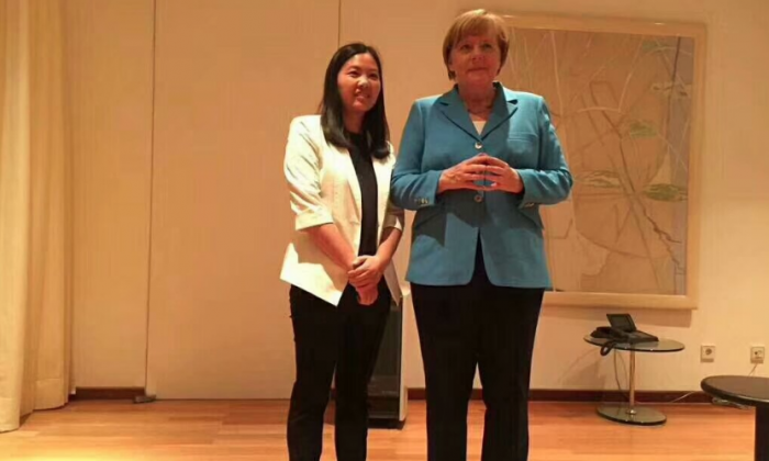 German Chancellor Angela Merkel with Xu Yan, wife of detained human rights lawyer Yu Wensheng. (Screenshot via Twitter)