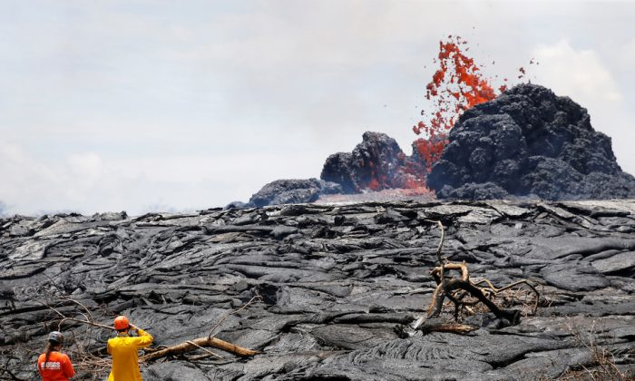 Sarah Conway, left, and Matt Patrick, both from USGS Hawaiian Volcano, observe lava erupting from a fissure in the Leilani Estates near Pahoa, Hawaii. (REUTERS/Marco Garcia)