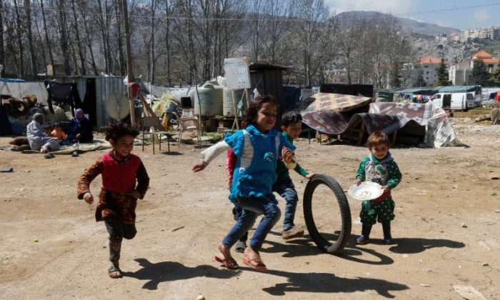 Syrian refugee children run in a tented settlement, in the town of Qab Elias, in Lebanon's Bekaa Valley, March 13, 2018. (Reuters/Mohamed Azakir)