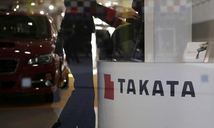 A woman stands next to a logo of Takata Corp at a showroom for vehicles in Tokyo, Japan, Nov. 6, 2015. (Reuters/Toru Hanai/File Photo)