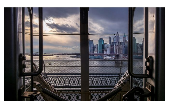 A photograph taken by Richard Koek of the Manhattan skyline as seen from between two subway cars on the Brooklyn Bridge. (Courtesy of Richard Koek)
