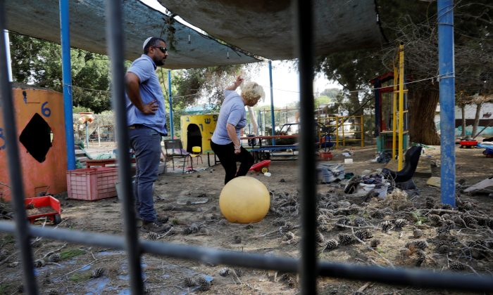 People stand in a kindergarten yard damaged by mortar shells fired from the Gaza Strip that landed near it, in a Kibbutz on the Israeli side of the Israeli-Gaza border, May 29, 2018. (Reuters/Amir Cohen)