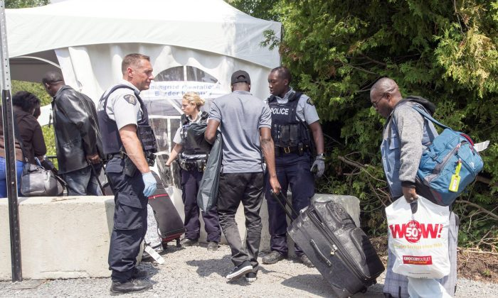 A group of asylum-seekers cross the Canadian border at Champlain, N.Y., on Aug. 4, 2017. (The Canadian Press/Ryan Remiorz)