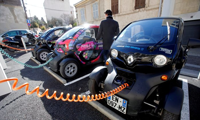 A man prepares to drive a Totem-Mobi electric car-sharing vehicle parked at a charging station in Marseille, France March 6, 2018. (Reuters/Jean-Paul Pelissie//File Photo)
