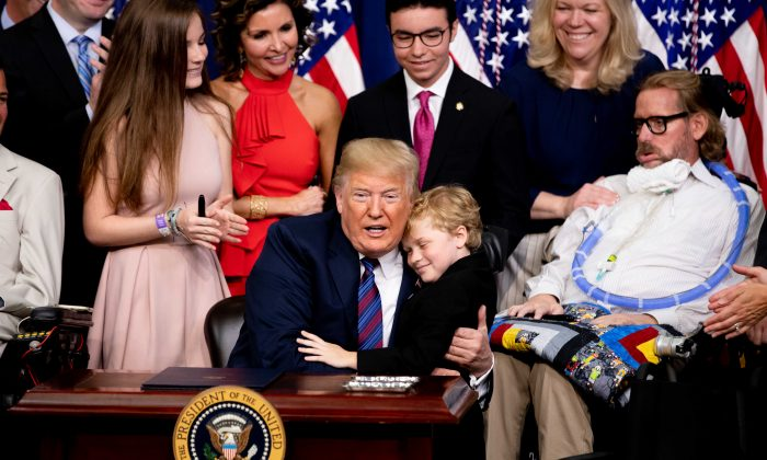 President Donald Trump hugs a boy with muscular dystrophy at the signing ceremony for the Right to Try legislation at the White House in Washington on May 30, 2018. (Samira Bouaou/Epoch Times)