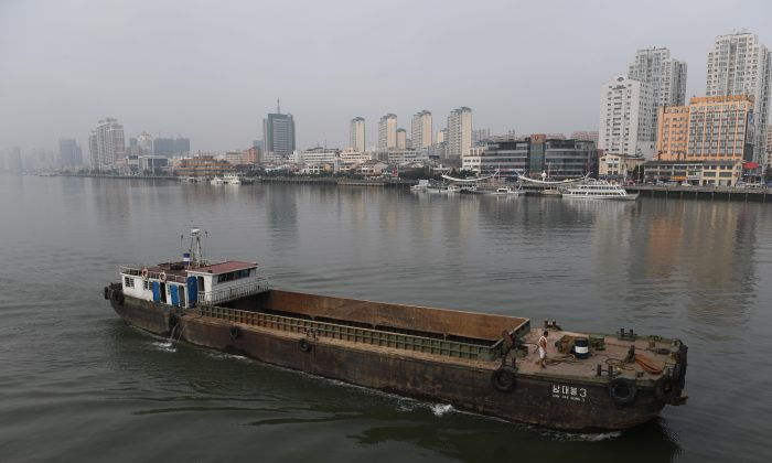 A North Korean ship passes in front of the Chinese border city of Dandong (at rear), in China's northeast Liaoning Province, on September 4, 2017. (Greg Baker/AFP/Getty Images)