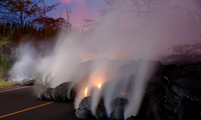 Volcanic gases rise from the Kilauea lava flow that crossed Pohoiki Road near Highway 132, near Pahoa, Hawaii, U.S., May 28, 2018. (Reuters/Marco Garcia)