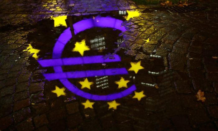 The euro sign in front of the former headquarters of the European Central Bank (ECB) is reflected in a puddle during heavy rain in Frankfurt, Germany, November 20, 2017.  Reuters/Kai Pfaffenbach)