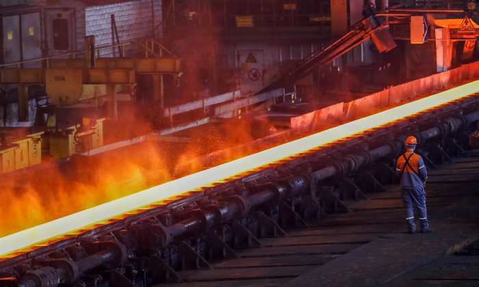 A red-hot steel plate passes through a press at the ArcelorMittal steel plant in Ghent, Belgium, May 22, 2018. (Reuters/Yves Herman/File Photo)