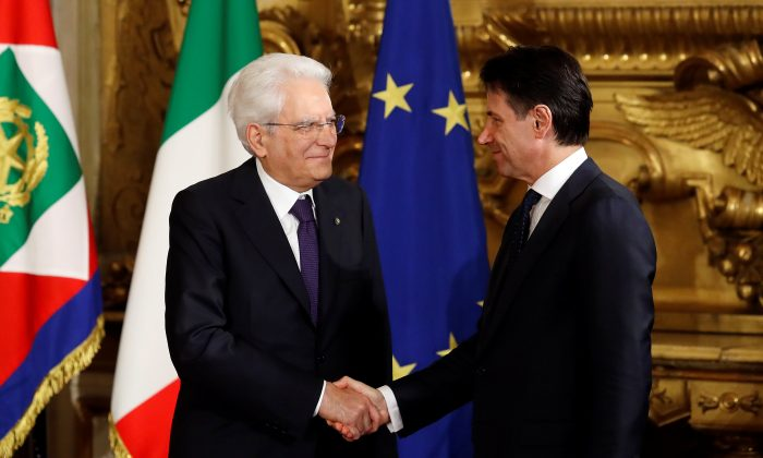 Italy's president Sergio Mattarella shakes hands with Prime Minister-designate Giuseppe Conte during the sworn-in ceremony at the Quirinal palace in Rome, Italy, June 1, 2018. (Reuters/Remo Casilli)