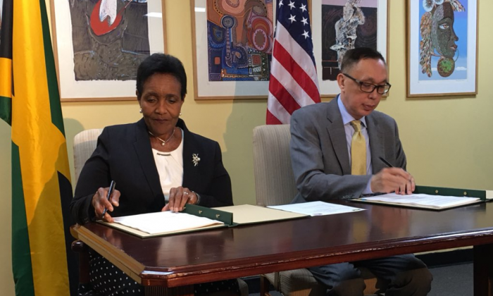 Charge' d' Affaires Eric Khant and Ambassador Marcia Gilbert-Roberts sign official CPC Agreement btw US and GOJ in Kingston. (US Embassy Jamaica)