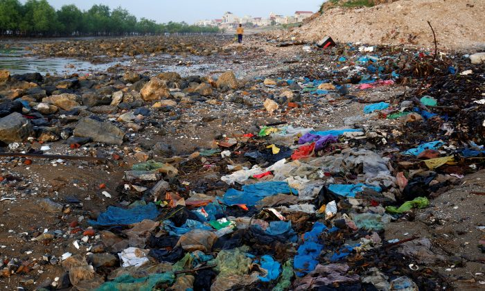 A woman walks at the beach covered with plastic waste in Thanh Hoa province, Vietnam Jun. 4, 2018. (REUTERS/Kham)