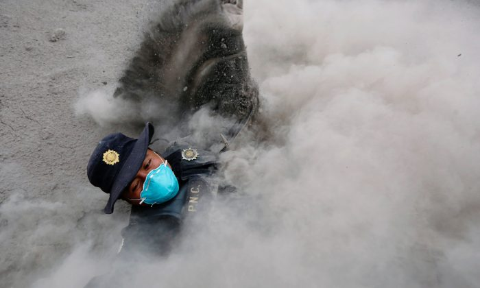 A police officer stumbles while running away from a new pyroclastic flow spewed by the Fuego volcano in the community of San Miguel Los Lotes in Escuintla, Guatemala, June 4, 2018. (Reuters/Luis Echeverria)