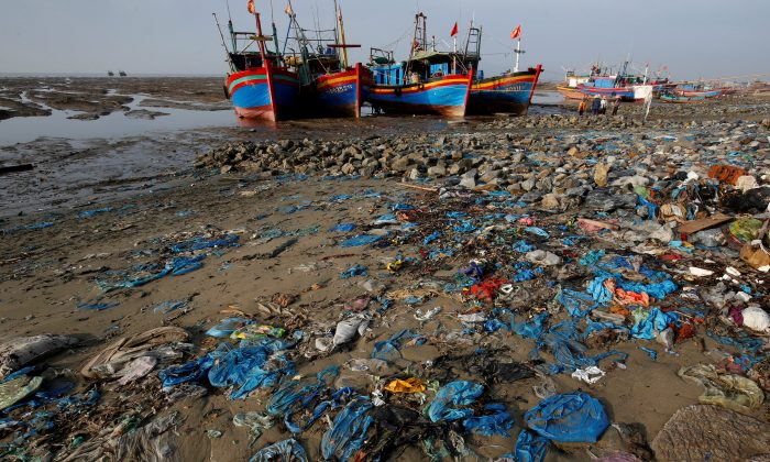 Fishing boats are seen on a beach covered with plastic waste in Thanh Hoa province, Vietnam June 4, 2018. (Reuters/Nguyen Huy Kham)