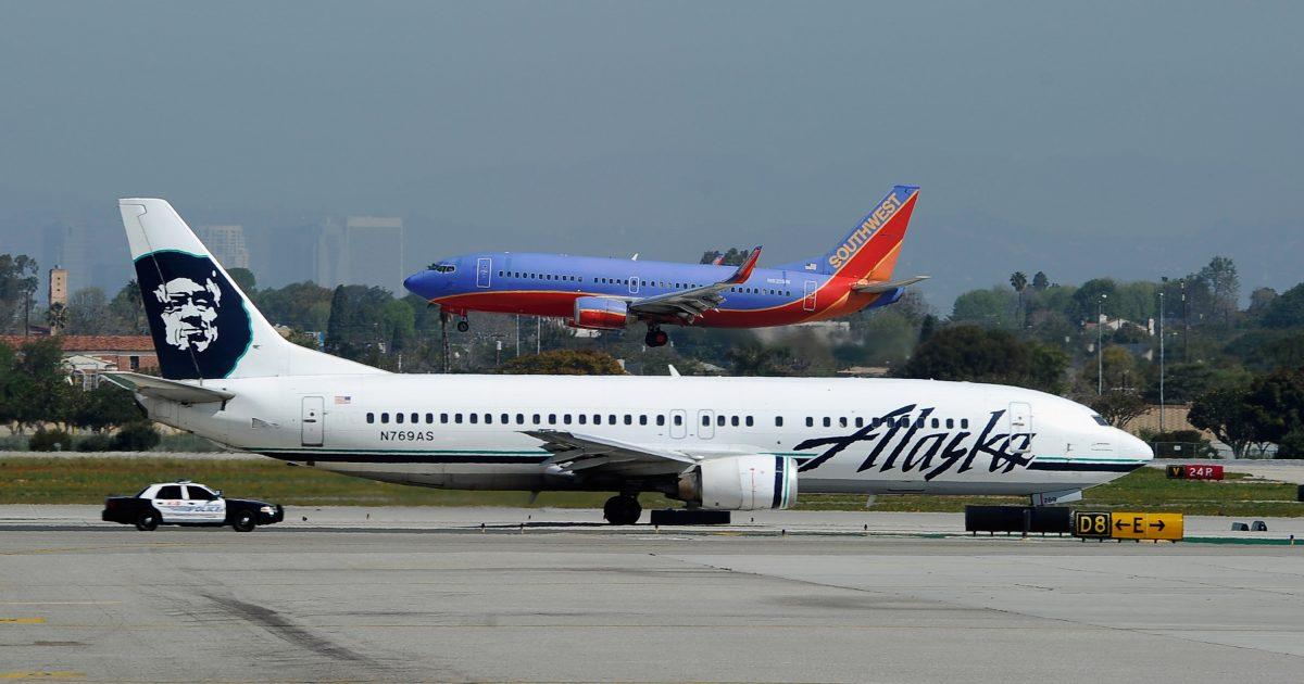 Southwest Plane flies past an Alaska Airlines jet on the runway
