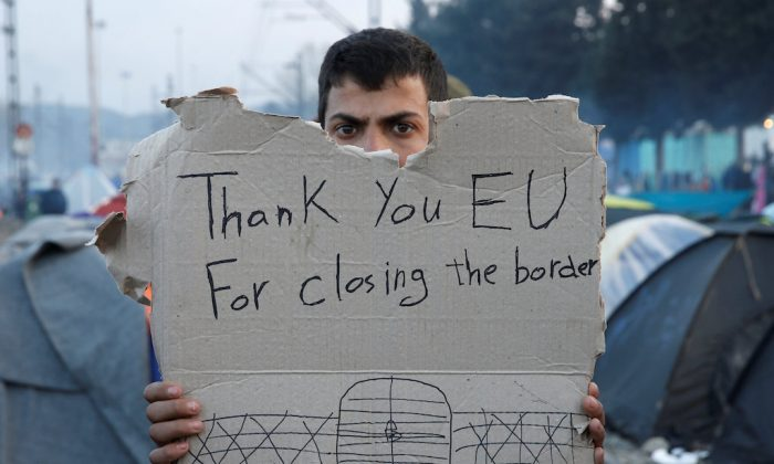 """A refguee holds a message, """"Thank you EU for closing the border"""" during a protest asking for the opening of borders at a makeshift camp at the Greek-Macedonian border near the village of Idomeni, Greece, Mar. 18, 2016.   (REUTERS/Alkis Konstantinidis/File Photo)"""