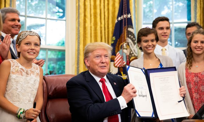 President Donald Trump participates in the signing ceremony for S. 292 – The Childhood Cancer Survivorship, Treatment, Access, and Research Act of 2018 in the Oval Office at the White House in Washington on June 5, 2018. (Samira Bouaou/The Epoch Times)