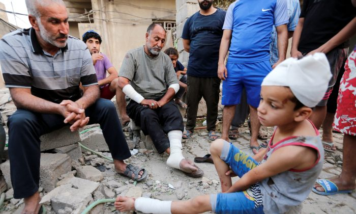 A man and his son, who were wounded, sit near the scene of an explosion in Baghdad's Sadr City district, Iraq June 7, 2018. (Wissm al-Okili/Reuters)
