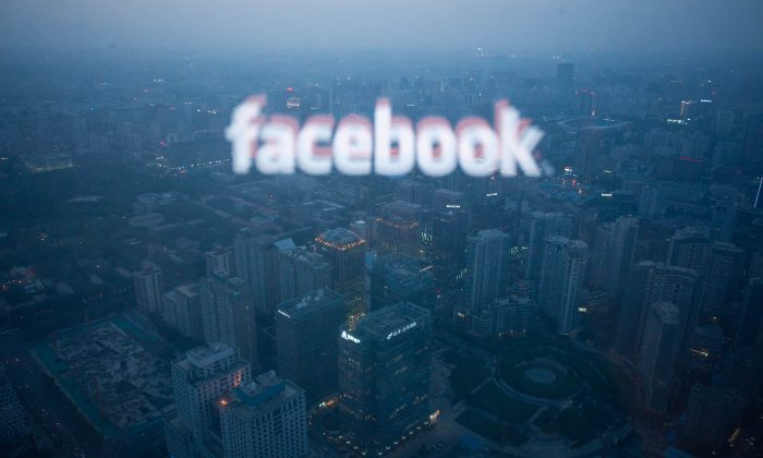 A computer screen displaying the logo of social networking site Facebook reflected in a window before the Beijing skyline on May 16, 2012. (Ed Jones/AFP/Getty Images)