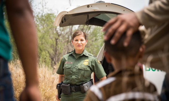 Marlene Castro, Supervisory Border Patrol Agent, speaks to a group of illegal border crossers, including a man with a child, near the Rio Grande at the U.S.–Mexico border in Hidalgo County, Texas, on May 26, 2017.  (Benjamin Chasteen/The Epoch Times)