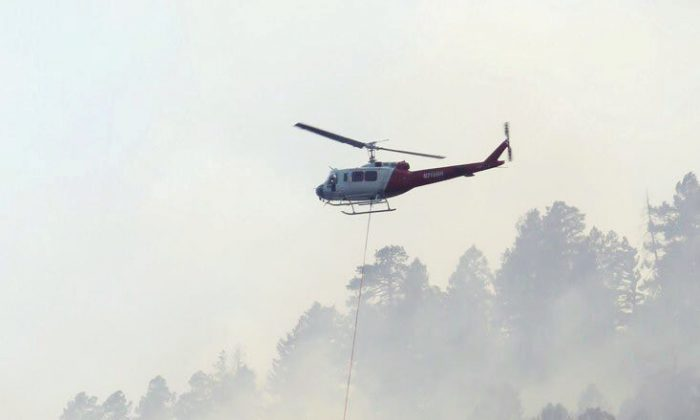 A helicopter drops water on the 416 Fire near Durango, Colorado, U.S. in this June 4, 2018 handout photo obtained by Reuters June 5, 2018.   (La Plata County/Handout via Reuters)