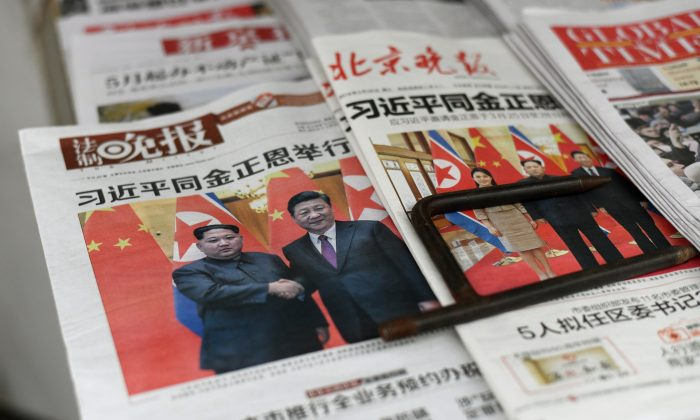 The front pages of Chinese newspapers showing images of Chinese leader Xi Jinping with North Korean leader Kim Jong Un, displayed at a newspaper stand in Beijing on March 28, 2018. (Fred Dufour/AFP/Getty Images)