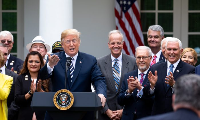 President Donald Trump participates in the signing ceremony for S. 2372 – VA Mission Act of 2018 in the Rose Garden of the White House in Washington on June 6, 2018. (Samira Bouaou/The Epoch Times