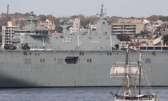 A boat sails near an Australian Navy vessel docked in Sydney on May 2, 2018. (Ludovic Marin/AFP/Getty Images)