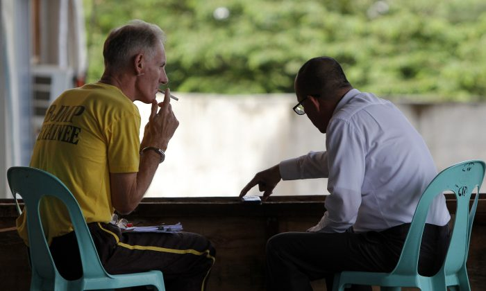Peter Scully of Australia (L), who was found guilty of rape and human trafficking in the Philippines, smokes a cigarette in Cagayan de Oro City on June 16, 2015. (STR/AFP/Getty Images)