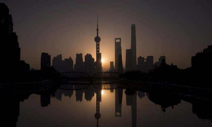 The sun rises behind the Shanghai skyline, overlooking the Pudong district on November 11, 2016. (Johannes Eisele/AFP/Getty Images)