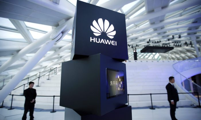 Security personnel stand near a pillar with the Huawei logo at a launch event for the Huawei MateBook in Beijing in a file photo. The Chinese telecommunications giant has established a strong presence in the Canadian market, which worries cyber security experts. (AP Photo/Mark Schiefelbein)