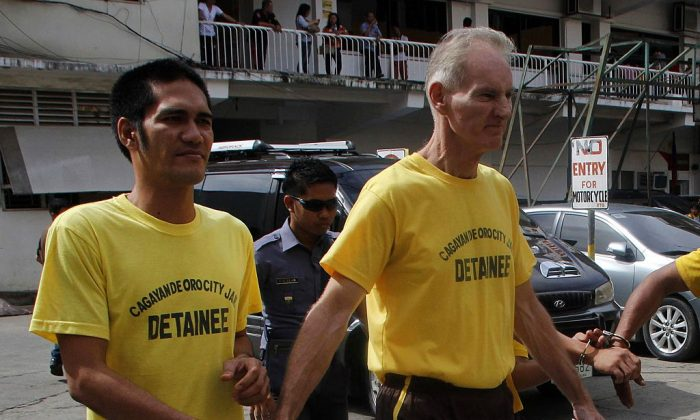 Peter Gerard Scully of Australia (R), accused of raping and trafficking in the Philippines, leaves the court handcuffed to another inmate (L) after his arraignment in Cagayan de Oro City, on the southern Philippine island of Mindanao on June 16, 2015. (STR/AFP/Getty Images)