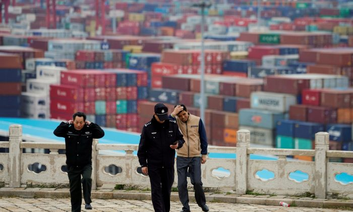 Security guards walk in front of containers at the Yangshan Deep Water Port in Shanghai, China, on April 24, 2018. (Aly Song/File Photo/Reuters)
