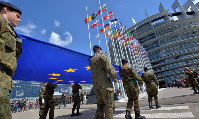 Soldiers of a Eurocorps detachment carry the European Union flag in front of the European Parliament in Strasbourg, eastern France on June 30, 2014. (Patrick Hertzog/AFP/Getty Images)
