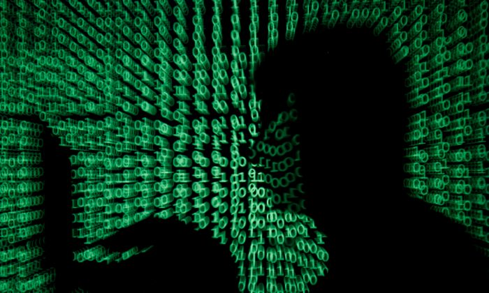 A man holds a laptop computer as cyber code is projected on him in this illustration picture taken on May 13, 2017. (Reuters/Kacper Pempel/File Photo)
