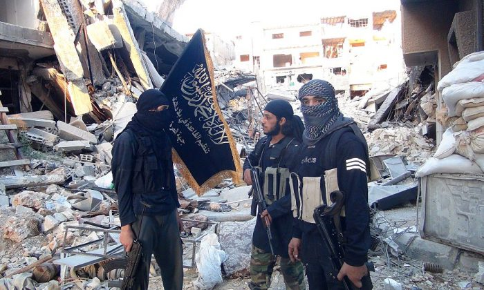 Terrorists from the al-Qaida group in the Levant, Al-Nusra Front, stand among destroyed buildings near the front line with Syrian government soldiers in  Yarmuk, Palestinian refugee camp, south of Damascus on Sept. 22, 2014. (Rami Al-Sayed/AFP/Getty Images)