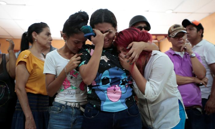 Family members and friends mourn the victims of a fire that broke out in a building in Managua, Nicaragua June 16, 2018. (Reuters/Oswaldo Rivas)