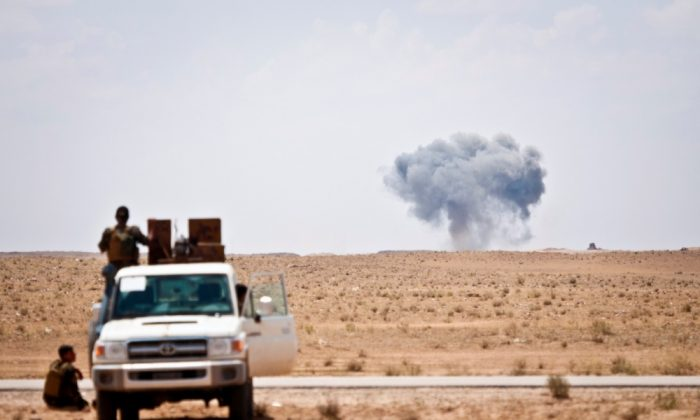 Syrian Democratic Forces watch as a coalition airstrike hits its target on a known Islamic State of Iraq and Syria location near the Iraq-Syria border, May 13, 2018. (DoD photo by Army Staff Sgt. Timothy R. Koster)